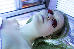 A woman laying in an artificial tanning bed.