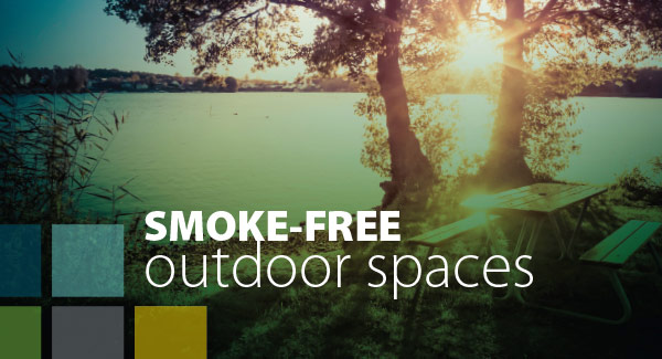 Photo of a sunset through trees with text: Smoke-free outdoor spaces