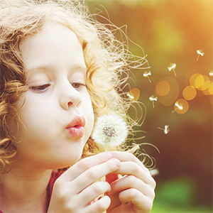 Photo of girl blowing on a dandelion