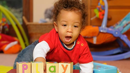 Photo of a toddler playing with blocks