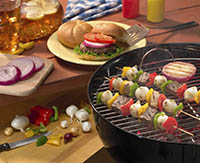 A hamburger with many topping options on a picnic table behind a barbeque grilling shish kabobs