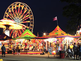 A carnival at night with people, games and a ferris wheel.