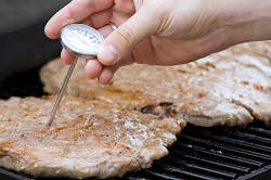 Probe thermometer being used to check internal meat temperature