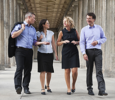 Four people walking together dressed in business atire.
