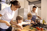A family of four preparing dinner with fresh vegetables.