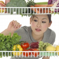 A person looking into a refrigerator at vegetables and fruit.