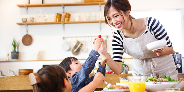Photo of mother cooking with small children