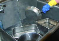A person rinsing the dishes in the second compartment sink.