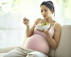 Photo of pregnant woman eating a salad
