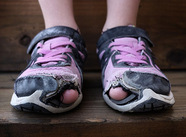 Photo of a child's shoes with holes in the toes