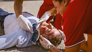 Photo of man lying on the ground with a large gash on his head, being treated by two people