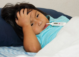 Photo of child in bed holding their head, with a thermometer in their mouth