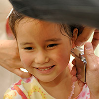 Photo of young girl getting ears pierced