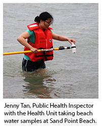 Public Health Inspector taking beach water samples at Sand Point Beach