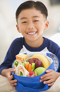 A child holding a lunch box full of healthy food, such as fruits, vegetables, and a wrap.