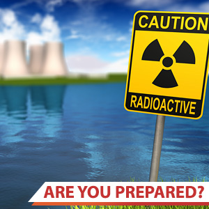 Photo of a caution: radioactive sign with a nuclear power plant in the background