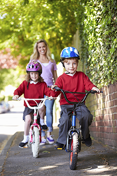 two children cycling down a sidewalk followed by a young woman.