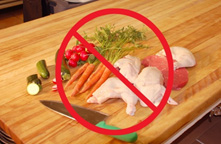 Photo of raw chicken on a cutting board with fruits and vegetables, overlaid by a circle/cross